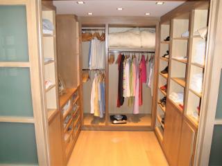 Dressing fermé par des portes coulissantes comprenant des étagères, une penderie et des tiroirs vitrés