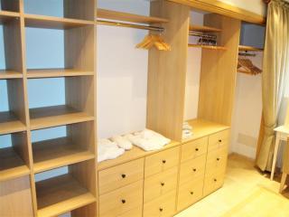 Dressing dissimulé par un rideau avec étagères, penderie et tiroirs