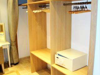Dressing dissimulé par un rideau avec étagères et penderies
